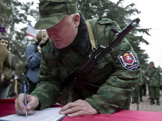 озброєний член першого підрозділу проросійських збройних сил підписує клятву під час церемонії приведення до присяги в сімферополі.
